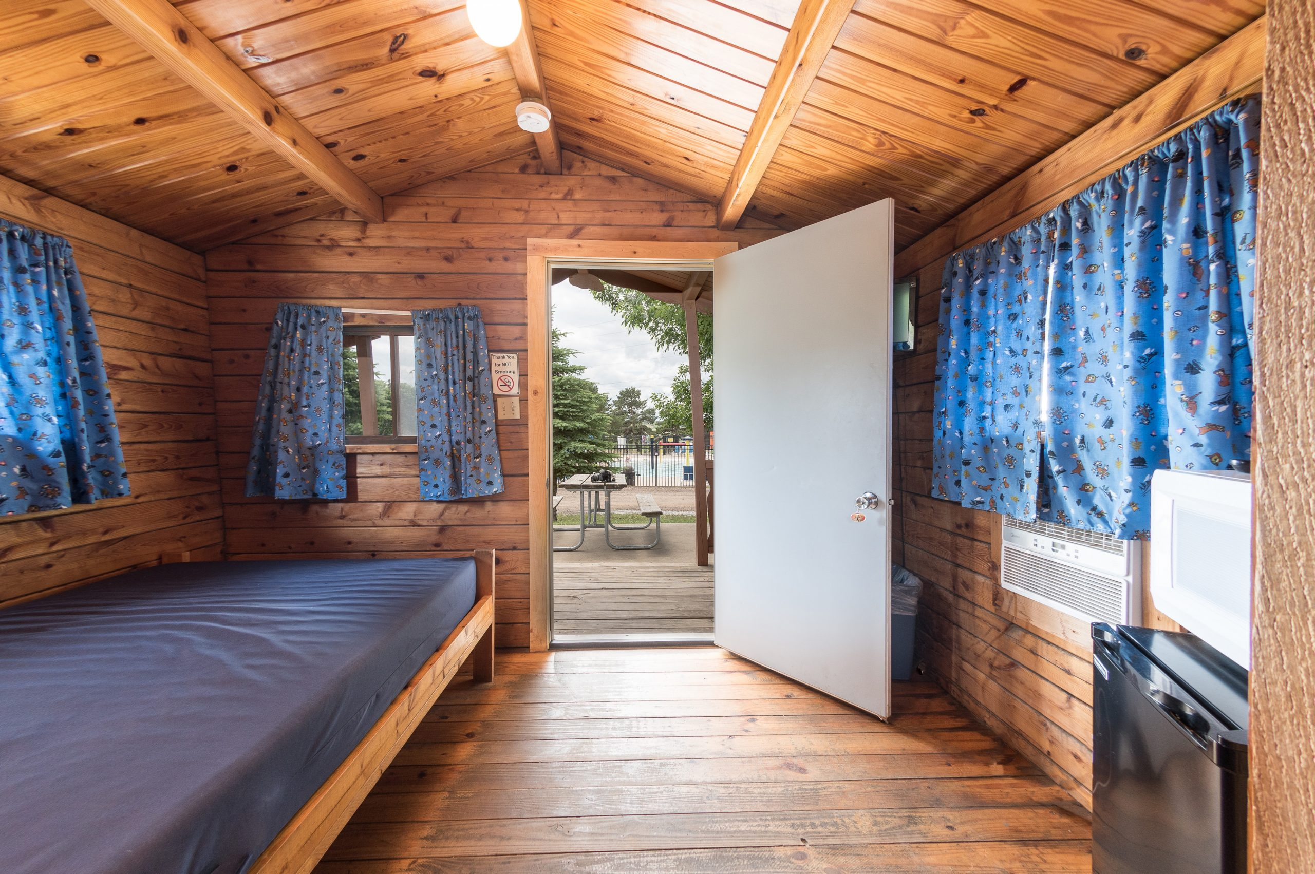Interior of rustic cabin, front room with full size bed, refridgerator and microwave